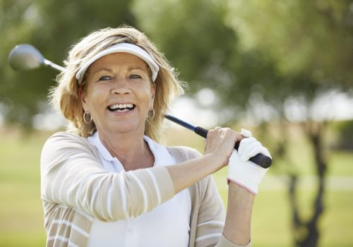 Senior woman playing golf on course